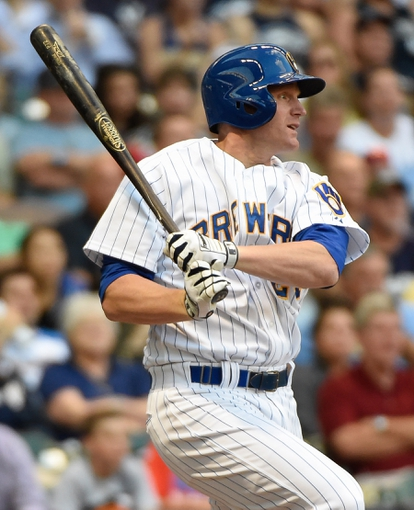 Jul 9, 2014; Milwaukee, WI, USA;  Milwaukee Brewers first baseman Lyle Overbay (24) hits a single to drive in a run in the second inning against the Philadelphia Phillies at Miller Park. Mandatory Credit: Benny Sieu-USA TODAY Sports