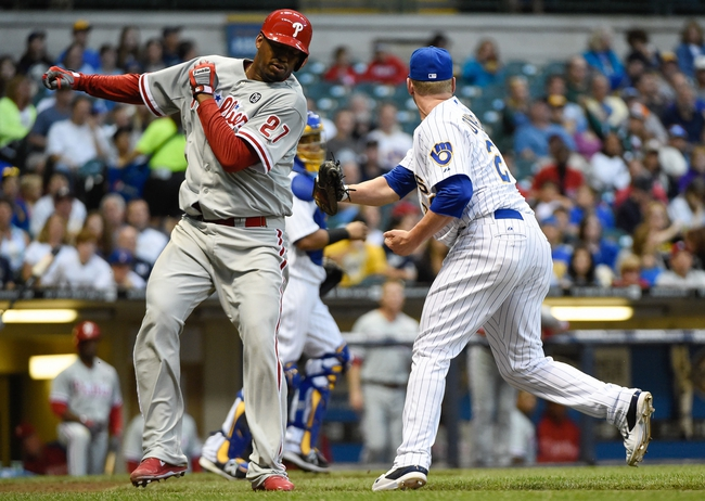Jul 9, 2014; Milwaukee, WI, USA; Philadelphia Phillies pitcher Roberto Hernandez (27) is tagged out by Milwaukee Brewers pitcher Kyle Lohse (26) after putting down a sacrifice bunt in the sixth inning at Miller Park. Mandatory Credit: Benny Sieu-USA TODAY Sports