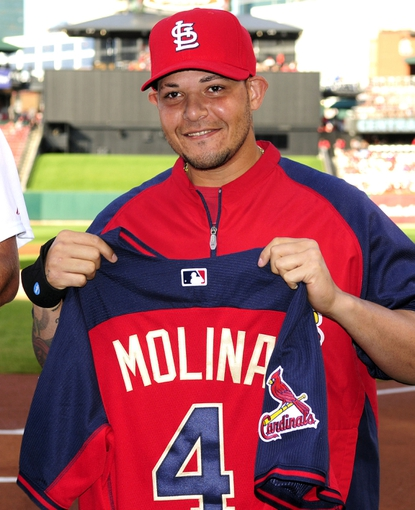 Jul 10, 2014; St. Louis, MO, USA; St. Louis Cardinals catcher Yadier Molina (4) poses with his All-Star jersey before a game against the Pittsburgh Pirates at Busch Stadium. Mandatory Credit: Jeff Curry-USA TODAY Sports