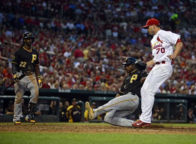 Jul 10, 2014; St. Louis, MO, USA; Pittsburgh Pirates right fielder Gregory Polanco (25) slides safely past St. Louis Cardinals relief pitcher Tyler Lyons (70) and scores on a passed ball during the sixth inning at Busch Stadium. Pirates defeated the Cardinals 9-1. Mandatory Credit: Jeff Curry-USA TODAY Sports