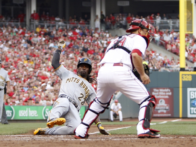 Jul 12, 2014; Cincinnati, OH, USA; Pittsburgh Pirates center fielder Andrew McCutchen (22) scores during the third inning against the Cincinnati Reds catcher Devin Mesoraco (39) at Great American Ball Park. Mandatory Credit: Frank Victores-USA TODAY Sports