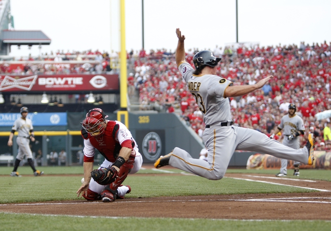 Jul 12, 2014; Cincinnati, OH, USA; Pittsburgh Pirates right fielder Travis Snider (23) scores during the first inning against the Cincinnati Reds catcher Devin Mesoraco (39) at Great American Ball Park. Mandatory Credit: Frank Victores-USA TODAY Sports