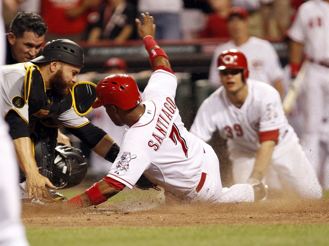 Jul 12, 2014; Cincinnati, OH, USA; Cincinnati Reds shortstop Ramon Santiago (7) is tagged out at home by the Pittsburgh Pirates catcher Russell Martin (55) during the tenth inning at Great American Ball Park. The Pirates defeated the Reds 6-5. Mandatory Credit: Frank Victores-USA TODAY Sports
