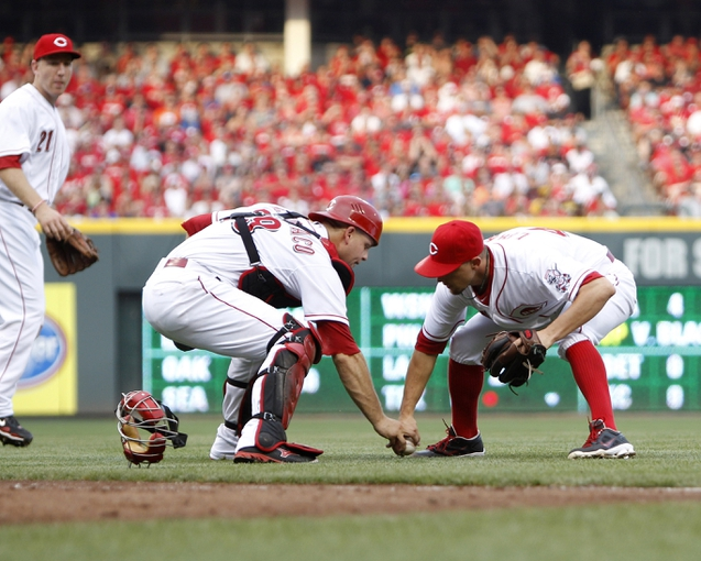 Jul 12, 2014; Cincinnati, OH, USA; Cincinnati Reds catcher Devin Mesoraco (39) and starting pitcher Mike Leake (44) bobble a bunt during the second inning against the Pittsburgh Pirates at Great American Ball Park. Mandatory Credit: Frank Victores-USA TODAY Sports