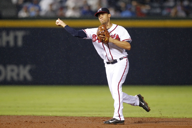 Jul 18, 2014; Atlanta, GA, USA; Atlanta Braves shortstop Andrelton Simmons (19) throws a runner out at first in the rain against the Philadelphia Phillies in the fifth inning at Turner Field. Mandatory Credit: Brett Davis-USA TODAY Sports
