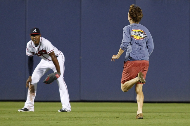 Jul 18, 2014; Atlanta, GA, USA; Atlanta Braves center fielder B.J. Upton (2) watches as a fan runs on the field during the ninth inning against the Philadelphia Phillies at Turner Field. The Braves defeated the Phillies 6-4.  Mandatory Credit: Brett Davis-USA TODAY Sports