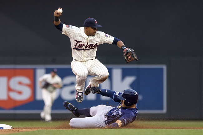 Jul 19, 2014; Minneapolis, MN, USA; Minnesota Twins shortstop Eduardo Escobar (5) jumps over Tampa Bay Rays left fielder Brandon Guyer (5) after making a force out at second base in the sixth inning at Target Field. Mandatory Credit: Jesse Johnson-USA TODAY Sports
