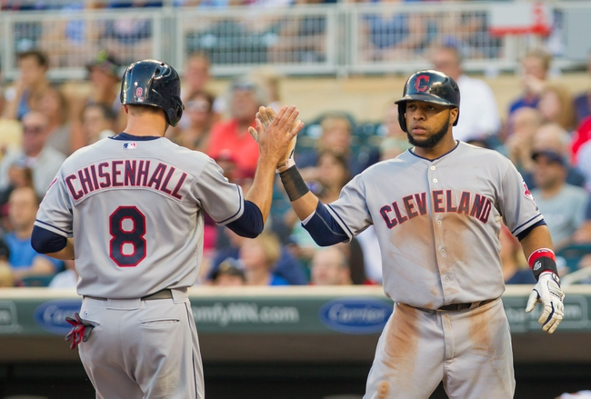 Jul 22, 2014; Minneapolis, MN, USA; Cleveland Indians first baseman Carlos Santana (41) congratulates third baseman Lonnie Chisenhall (8) after he scores in the second inning against the Minnesota Twins at Target Field. Mandatory Credit: Brad Rempel-USA TODAY Sports