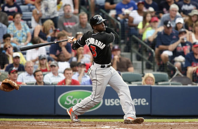 Jul 24, 2014; Atlanta, GA, USA; Miami Marlins shortstop Adeiny Hechavarria (3) hits an RBI single scoring center fielder Marcell Ozuna (not pictured) in the fifth inning of their game against the Atlanta Braves at Turner Field. Mandatory Credit: Jason Getz-USA TODAY Sports