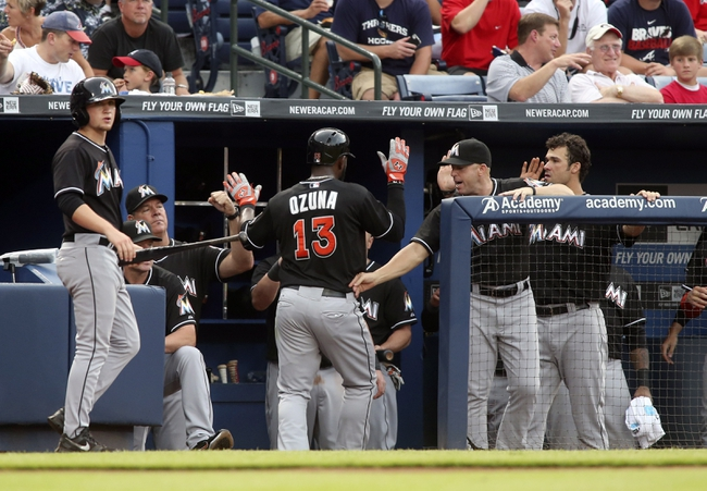 Jul 24, 2014; Atlanta, GA, USA; Miami Marlins center fielder Marcell Ozuna (13) celebrates scoring on a hit by shortstop Adeiny Hechavarria (not pictured) in the fifth inning of their game against the Atlanta Braves at Turner Field. Mandatory Credit: Jason Getz-USA TODAY Sports