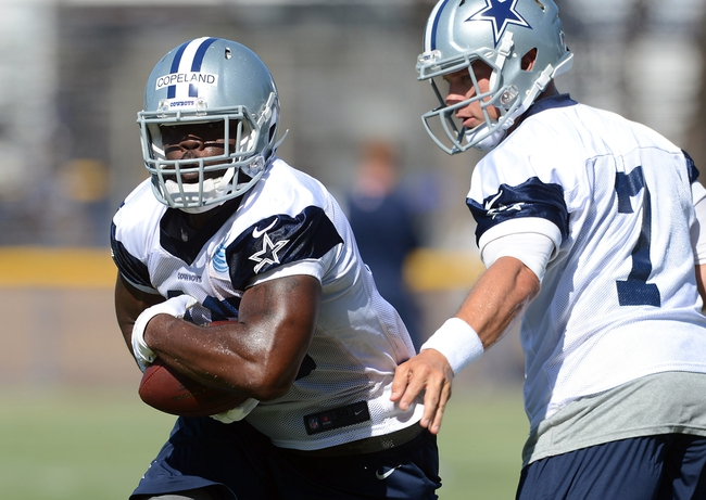 Jul 24, 2014; Oxnard, CA, USA; Dallas Cowboys quarterback Caleb Hanie (7) hands off to fullback J.C. Copeland (48) during training camp at the River Ridge Playing Fields.  Mandatory Credit: Jayne Kamin-Oncea-USA TODAY Sports