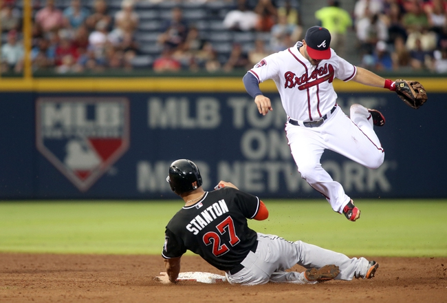 Jul 24, 2014; Atlanta, GA, USA; Atlanta Braves second baseman Tommy La Stella (7) avoids the collision with Miami Marlins right fielder Giancarlo Stanton (27) on a double play in the 6th inning of their game at Turner Field. Marlins won 3-2. Mandatory Credit: Jason Getz-USA TODAY Sports