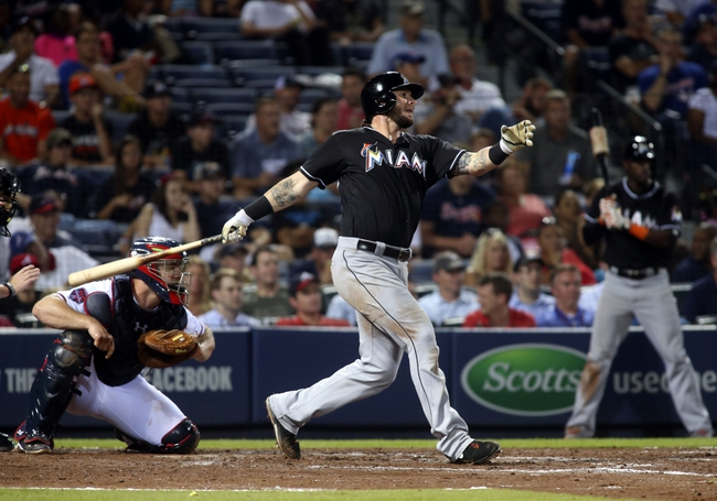 Jul 24, 2014; Atlanta, GA, USA; Miami Marlins catcher Jarrod Saltalamacchia (39) hits an RBI single scoring center fielder Marcell Ozuna (not pictured) as Atlanta Braves catcher Evan Gattis (24) is shown on the play in the ninth inning of their game at Turner Field. Marlins won 3-2. Mandatory Credit: Jason Getz-USA TODAY Sports