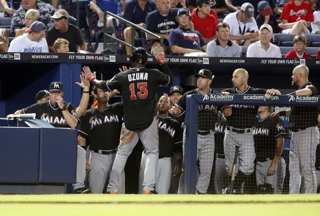 Jul 24, 2014; Atlanta, GA, USA; Miami Marlins center fielder Marcell Ozuna (13) celebrates with teammates after scoring a run off of a single by Miami Marlins catcher Jarrod Saltalamacchia (not pictured) in the ninth inning of their game against the Atlanta Braves at Turner Field. Marlins won 3-2. Mandatory Credit: Jason Getz-USA TODAY Sports