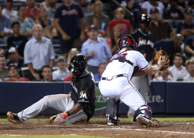 Jul 24, 2014; Atlanta, GA, USA; Miami Marlins center fielder Marcell Ozuna (13) scores ahead of the tag from Atlanta Braves catcher Evan Gattis (24) on a single by Miami Marlins catcher Jarrod Saltalamacchia (not pictured) in the ninth inning of their game at Turner Field. Marlins won 3-2. Mandatory Credit: Jason Getz-USA TODAY Sports