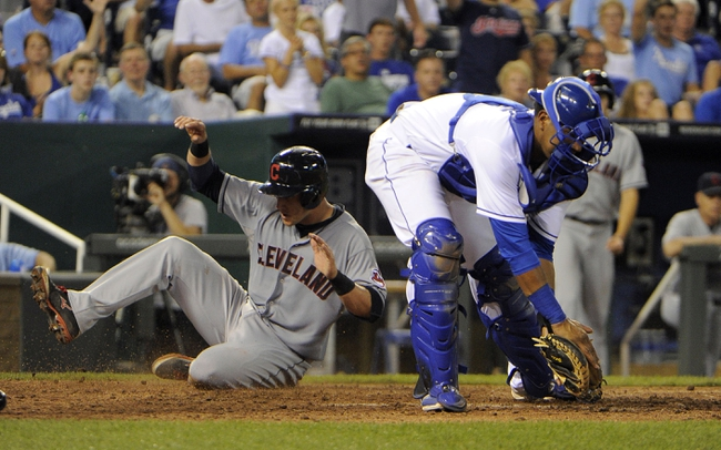 Jul 25, 2014; Kansas City, MO, USA; Cleveland Indians catcher Yan Gomes (10) scores against Kansas City Royals catcher Salvador Perez (13) on a sacrifice fly in the seventh inning at Kauffman Stadium. Mandatory Credit: John Rieger-USA TODAY Sports