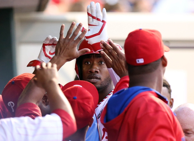 Jul 25, 2014; Philadelphia, PA, USA; Philadelphia Phillies left fielder Domonic Brown (9) is congratulated in the dugout after scoring in the third inning of a game against the Arizona Diamondbacks at Citizens Bank Park. Mandatory Credit: Bill Streicher-USA TODAY Sports