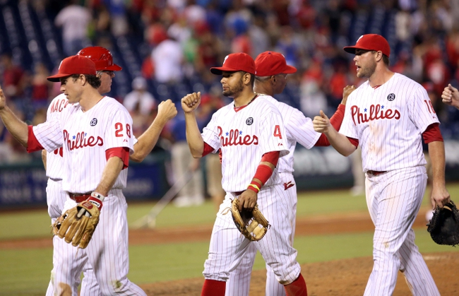 Jul 25, 2014; Philadelphia, PA, USA; Philadelphia Phillies second baseman Chase Utley (26) and shortstop Andres Blanco (4) and left fielder Darin Ruf (18) high five team mates at the conclusion of a game against the Arizona Diamondbacks at Citizens Bank Park. The Phillies won 9-5. Mandatory Credit: Bill Streicher-USA TODAY Sports