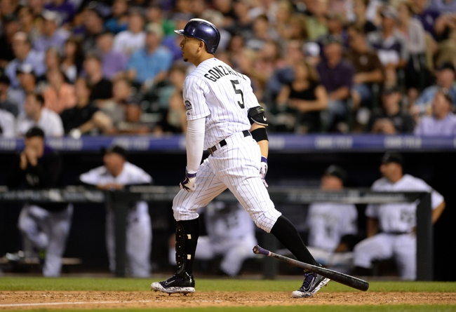 Jul 25, 2014; Denver, CO, USA; Colorado Rockies left fielder Carlos Gonzalez (5) watches his two run home run in the seventh inning against the Pittsburgh Pirates at Coors Field. Mandatory Credit: Ron Chenoy-USA TODAY Sports