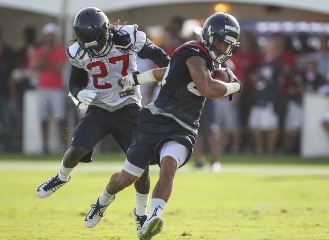 Jul 26, 2014; Houston, TX, USA; Houston Texans wide receiver Kofi Hughes (83) catches a pass as defensive back Josh Victorian (27) defends during training camp at Houston Methodist Training Center. Mandatory Credit: Troy Taormina-USA TODAY Sports