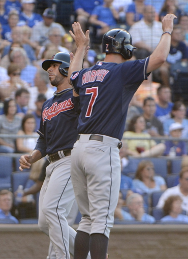Jul 26, 2014; Kansas City, MO, USA; Cleveland Indians third baseman Mike Aviles (4) is congratulated by right fielder David Murphy (7) after scoring against the Kansas City Royals in the second inning at Kauffman Stadium. Mandatory Credit: John Rieger-USA TODAY Sports