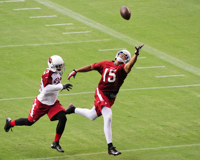 Jul 26, 2014; Tempe, AZ, USA; Arizona Cardinals wide receiver Michael Floyd (15) reaches for a catch as defensive back Bryan McCann (23) defnds during training camp at University of Phoenix. Mandatory Credit: Matt Kartozian-USA TODAY Sports