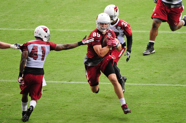 Jul 26, 2014; Tempe, AZ, USA; Arizona Cardinals tight end John Carlson (89) runs with the ball as defensive back Eddie Whitley (41) and free safety Anthony Walters (37) defend during training camp at University of Phoenix. Mandatory Credit: Matt Kartozian-USA TODAY Sports