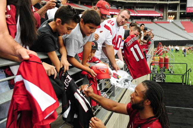 Jul 26, 2014; Tempe, AZ, USA; Arizona Cardinals wide receiver Larry Fitzgerald (11) signs autographs for fans during training camp at University of Phoenix. Mandatory Credit: Matt Kartozian-USA TODAY Sports