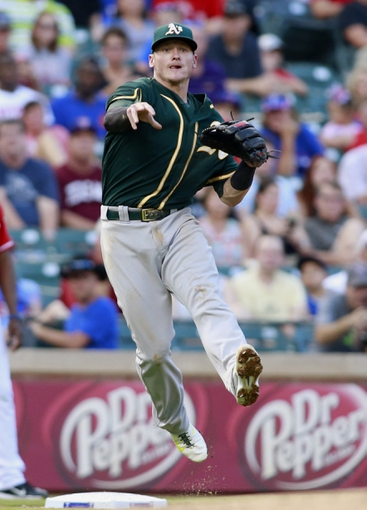 Jul 26, 2014; Arlington, TX, USA; Oakland Athletics third baseman Josh Donaldson (20) throws  out a Texas Rangers third baseman in the fourth inning at Globe Life Park in Arlington. Mandatory Credit: Tim Heitman-USA TODAY Sports