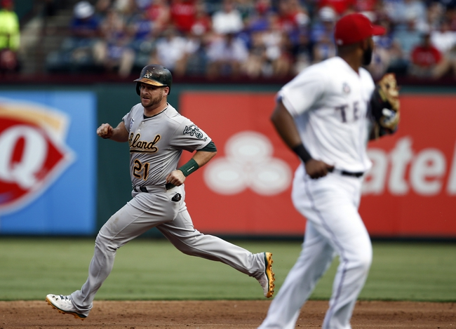 Jul 27, 2014; Arlington, TX, USA; Oakland Athletics designated hitter Stephen Vogt (21) runs to second on his way for an RBI double as Texas Rangers shortstop Elvis Andrus (1) looks on during the second inning of a baseball game at Globe Life Park in Arlington. Mandatory Credit: Jim Cowsert-USA TODAY Sports