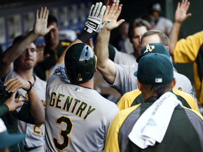 Jul 27, 2014; Arlington, TX, USA; Oakland Athletics center fielder Craig Gentry (3) is congratulated by teammates in the dugout after scoring a run against the Texas Rangers during the fifth inning of a baseball game at Globe Life Park in Arlington. Mandatory Credit: Jim Cowsert-USA TODAY Sports