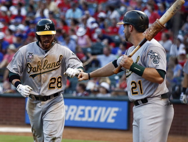 Jul 27, 2014; Arlington, TX, USA; Oakland Athletics second baseman Eric Sogard (28) is congratulated after scoring by designated hitter Stephen Vogt (21) against the Texas Rangers during the fifth inning of a baseball game at Globe Life Park in Arlington. Mandatory Credit: Jim Cowsert-USA TODAY Sports