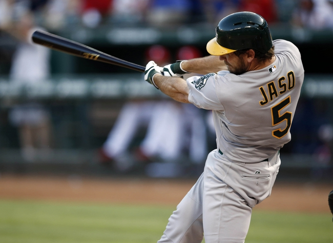 Jul 27, 2014; Arlington, TX, USA; Oakland Athletics catcher John Jaso (5) follows through for a two-run double against the Texas Rangers during the fifth inning of a baseball game at Globe Life Park in Arlington. Mandatory Credit: Jim Cowsert-USA TODAY Sports