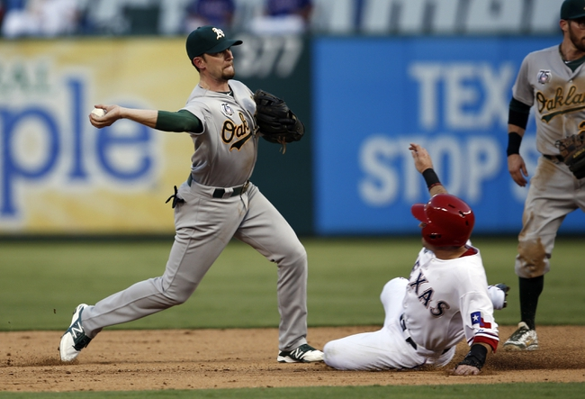 Jul 27, 2014; Arlington, TX, USA; Oakland Athletics shortstop Jed Lowrie (8) throws to first turning the first half of a double play on Texas Rangers left fielder Daniel Robertson (19) during the fifth inning of a baseball game at Globe Life Park in Arlington. Mandatory Credit: Jim Cowsert-USA TODAY Sports