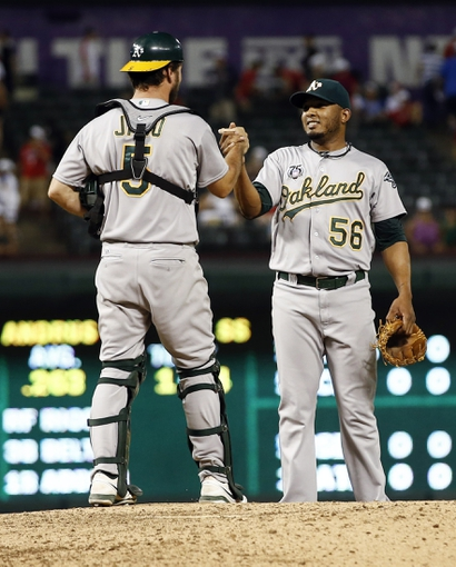 Jul 27, 2014; Arlington, TX, USA; Oakland Athletics relief pitcher Fernando Abad (56) and catcher John Jaso (5) congratulate each other following their teams 9-3 win over the Texas Rangers at Globe Life Park in Arlington. Mandatory Credit: Jim Cowsert-USA TODAY Sports