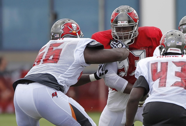 Jul 28, 2014; Tampa, FL, USA; Tampa Bay Buccaneers defensive tackle Gerald McCoy (93) rushes as offensive guard Patrick Omameh (66) blocks during training camp at One Buc Place. Mandatory Credit: Kim Klement-USA TODAY Sports