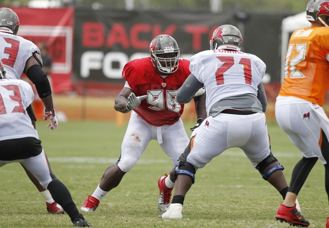 Jul 28, 2014; Tampa, FL, USA; Tampa Bay Buccaneers defensive tackle Clinton McDonald (98) rushes as Tampa Bay Buccaneers offensive guard Kadeem Edwards (71) blocks during training camp at One Buc Place. Mandatory Credit: Kim Klement-USA TODAY Sports