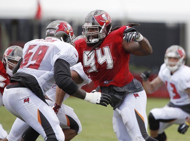 Jul 28, 2014; Tampa, FL, USA; Tampa Bay Buccaneers defensive end Adrian Clayborn (94) rushes as tackle Demar Dotson (69) blocks during training camp at One Buc Place. Mandatory Credit: Kim Klement-USA TODAY Sports