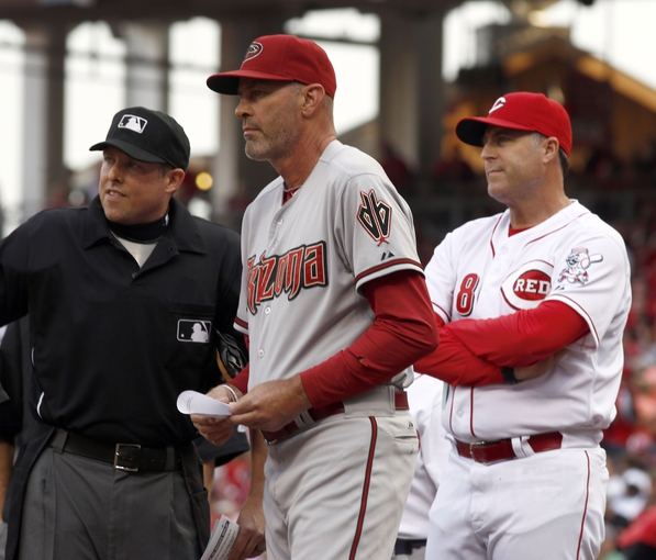 Jul 28, 2014; Cincinnati, OH, USA; Arizona Diamondbacks manager Kirk Gibson (23) and Cincinnati Reds manager Bryan Price (38) stand at home plate with home plate umpire Hal Gibson (left) at the beginning of a game at Great American Ball Park. Mandatory Credit: David Kohl-USA TODAY Sports