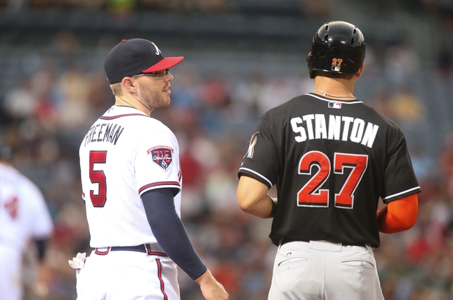 Jul 24, 2014; Atlanta, GA, USA; Atlanta Braves first baseman Freddie Freeman (5) talks with Miami Marlins right fielder Giancarlo Stanton (27) after Stanton hit a single in the sixth inning of their game at Turner Field. Marlins won 3-2. Mandatory Credit: Jason Getz-USA TODAY Sports