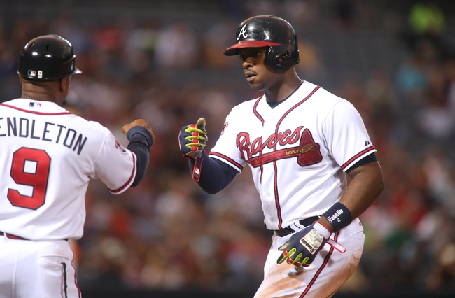 Jul 24, 2014; Atlanta, GA, USA; Atlanta Braves left fielder Justin Upton (8) celebrates his single with Atlanta Braves first base coach Terry Pendleton (9) in the sixth inning of their game against the Miami Marlins at Turner Field. Marlins won 3-2. Mandatory Credit: Jason Getz-USA TODAY Sports