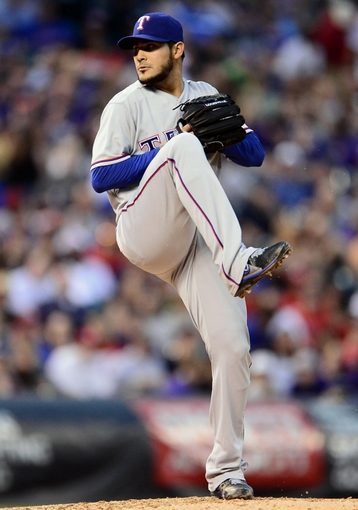 May 5, 2014; Denver, CO, USA; Texas Rangers starting pitcher Martin Perez (33) prepares to throw in the fourth inning against the Colorado Rockies at Coors Field. Mandatory Credit: Ron Chenoy-USA TODAY Sports