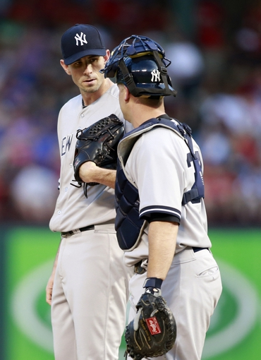 Jul 29, 2014; Arlington, TX, USA; New York Yankees starting pitcher Brandon McCarthy (38) talks with  catcher Brian McCann (34) in the third inning against the Texas Rangers at Globe Life Park in Arlington. Mandatory Credit: Tim Heitman-USA TODAY Sports
