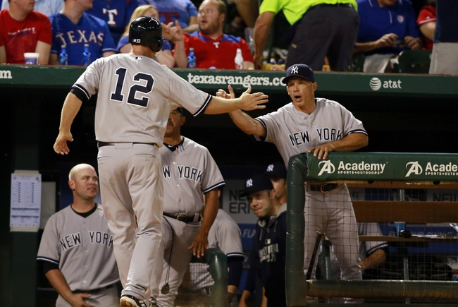 Jul 29, 2014; Arlington, TX, USA;  New York Yankees third baseman Chase Headley (12) is congratulated after scoring a run by manager Joe Girardi (28) in the sixth inning against the Texas Rangers at Globe Life Park in Arlington. Mandatory Credit: Tim Heitman-USA TODAY Sports