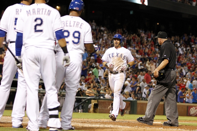 Jul 29, 2014; Arlington, TX, USA; Texas Rangers first baseman J.P. Arencibia (7) crosses home plate after hitting a grand slam home run in the seventh inning against the New York Yankees at Globe Life Park in Arlington. New York beat Texas 12-11. Mandatory Credit: Tim Heitman-USA TODAY Sports