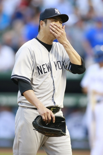 Jul 30, 2014; Arlington, TX, USA; New York Yankees starting pitcher Hiroki Kuroda (18) walks off the mound after the first inning against the Texas Rangers at Globe Life Park in Arlington. Mandatory Credit: Tim Heitman-USA TODAY Sports