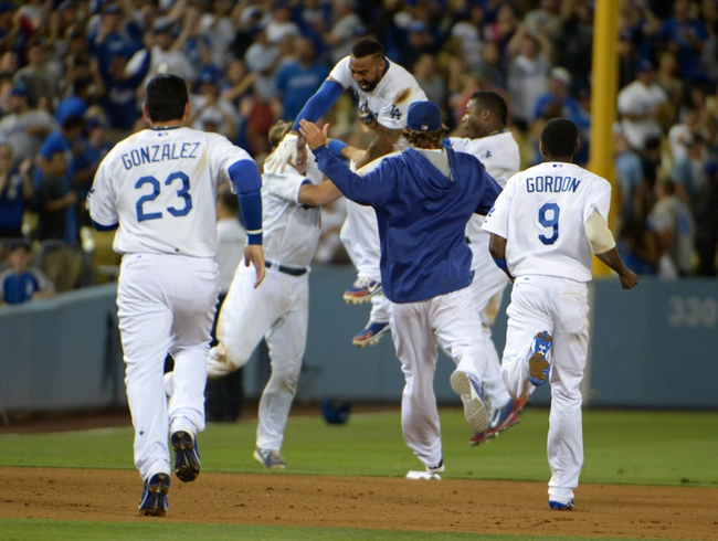 Jul 30, 2014; Los Angeles, CA, USA; Los Angeles Dodgers right fielder Matt Kemp (27) celebrates with teammates Adrian Gonzalez (23), A.J. Ellis (17), Yasiel Puig (66) and Dee Gordon (9) a hitting a walk-off single in the 10th inning against the Atlanta Braves at Dodger Stadium. The Dodgers defeated the Braves 2-1 in 10 innings. Mandatory Credit: Kirby Lee-USA TODAY Sports