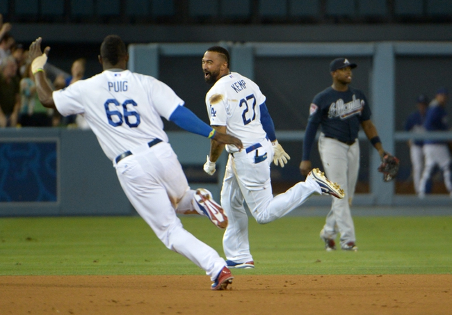 Jul 30, 2014; Los Angeles, CA, USA; Los Angeles Dodgers right fielder Matt Kemp (27) celebrates with center fielder Yasiel Puig (66) on a walk-off single in the 10th inning against the Atlanta Braves at Dodger Stadium. The Dodgers defeated the Braves 2-1 in 10 innings. Mandatory Credit: Kirby Lee-USA TODAY Sports