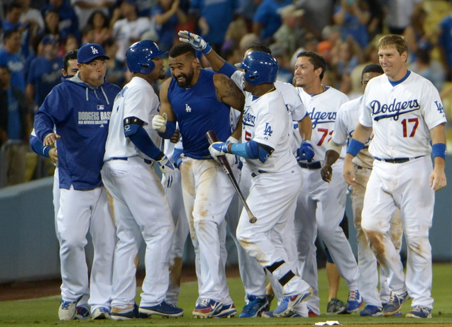 Jul 30, 2014; Los Angeles, CA, USA; Los Angeles Dodgers right fielder Matt Kemp (27) celebrates with teammates Hyun-Jin Ruy (99), Juan Uribe (5), Miguel Rojas (72) and A.J. Ellis (17) after a hitting a walk-off single in the 10th inning against the Atlanta Braves at Dodger Stadium. The Dodgers defeated the Braves 2-1 in 10 innings. Mandatory Credit: Kirby Lee-USA TODAY Sports