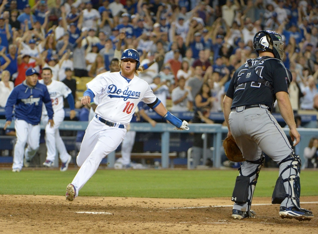Jul 30, 2014; Los Angeles, CA, USA; Los Angeles Dodgers infielder Justin Turner (10) slides into home plate to score the winning run in the 10th inning as Atlanta Braves catcher Evan Gattis (24) watches at Dodger Stadium. The Dodgers defeated the Braves 2-1 in 10 innings. Mandatory Credit: Kirby Lee-USA TODAY Sports